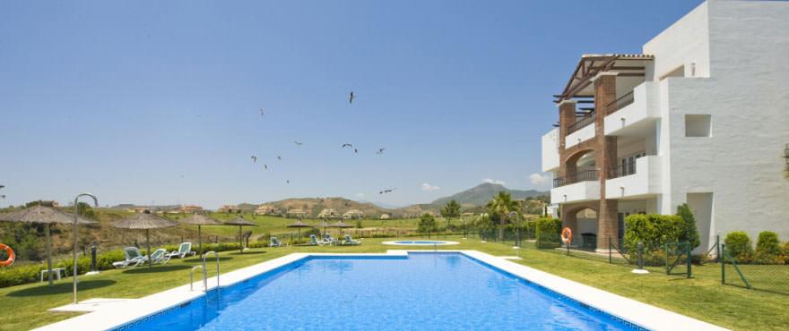 Vista de fachadas lateral, piscina y jardin comunitarios en Los Robles de los Arqueros