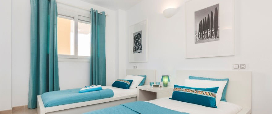 Bedroom with two beds in Cala Magrana III complex with apartments for sale