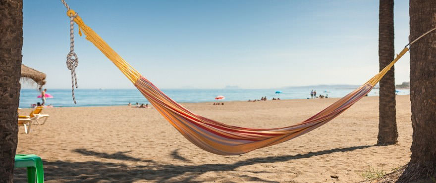 Hammock on the beach in Marbella next to Los Aruqeros Beach complex with apartments for sale