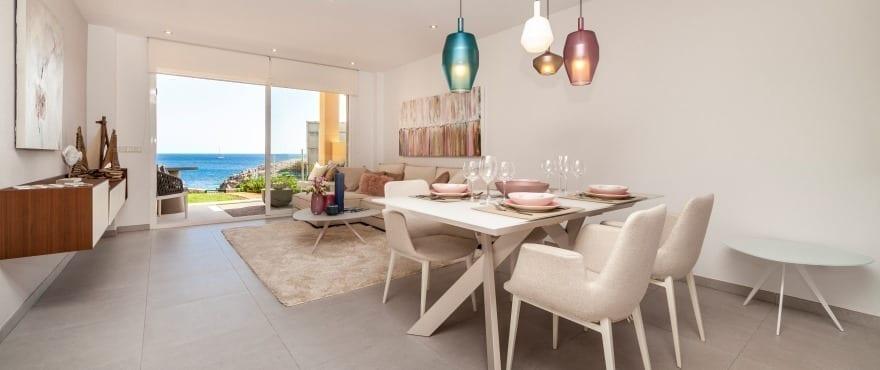 Salon-salle à manger lumineux à Blue Cove, avec grande terrasse donnant sur la mer