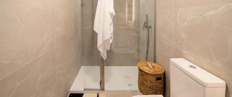 Baño moderno y completo en Iconic, con mamparas instaladas